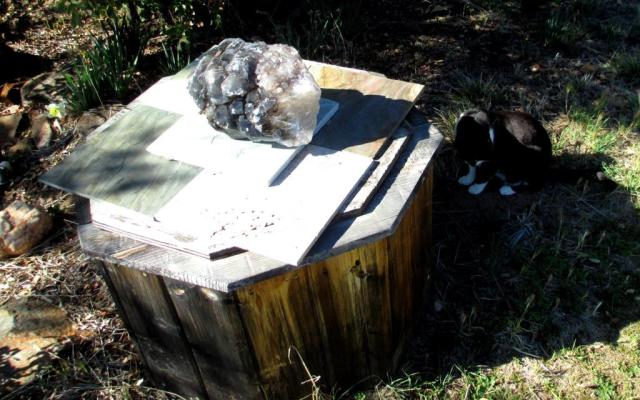 She's sitting next to a 30-pound smoky quartz skeleton crystal with hemetite inclusions, on top of some slate tiles.
