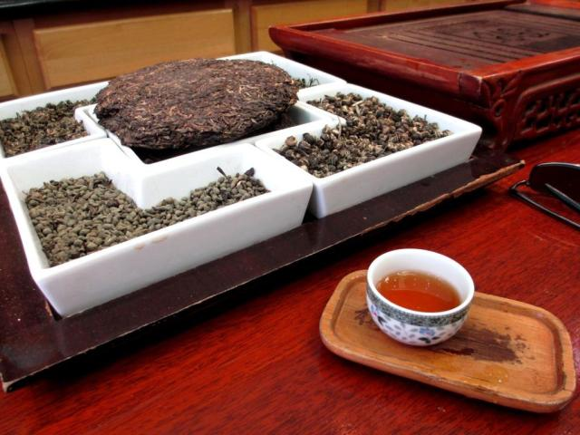 The wooden tray you see has slots in it to catch poured-over tea, a brewing technique. The ceramic dish holds samples of different textures of teas.