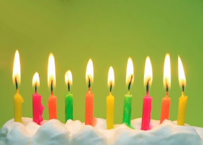 10 lit birthday candles in bright colors with green background